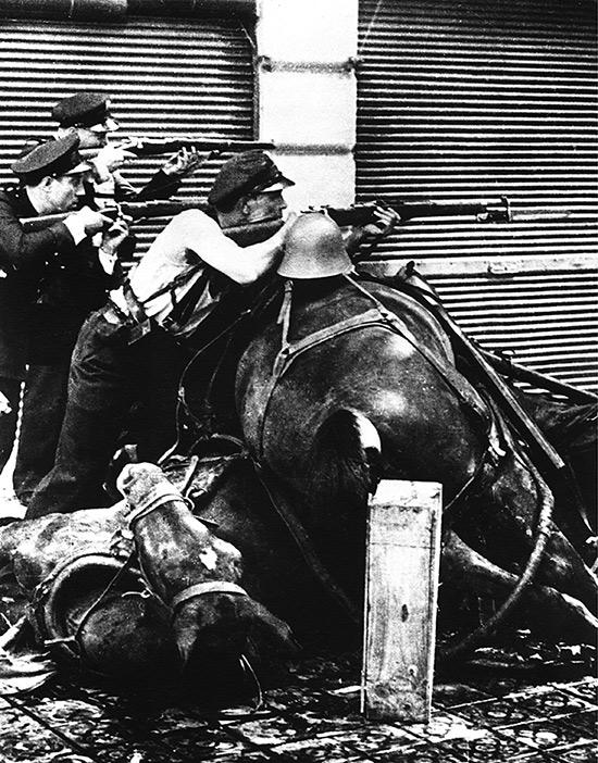 Agusti-Centelles-exposicion-Guardias-de-asalto-tras-una-barricada-de-caballos-muertos